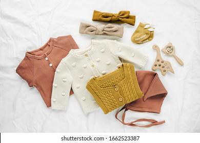 Set of  baby rompers, hat,  hairband and  knitted jumper on white bed. Fashion  baby clothes and accessories. Flat lay, top view