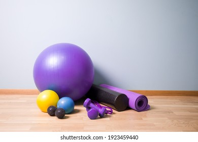 Set of balls of different sizes, foam roll and yogamat on wooden floor. Professional equipment for fitness and myofascial release.