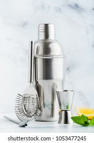 Set of bar accessories for cocktail making. Shaker, jigger, strainer, spoon on a marble background. lemon and mint leaves