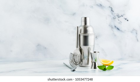 Set of bar accessories for cocktail making. Shaker, jigger, strainer, spoon on a marble background. lemon and mint leaves. copy space