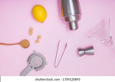Set of bar accessories for cocktail making. Shaker, jigger, and other bar tools with lemon and sugar on pink background