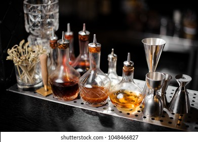 Set of bar equipment and bottles with tasty and sweet syrups arranged on the bar counter