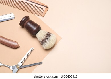 Set of barber's equipment on beige background, flat lay. Space for text