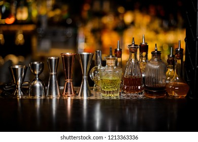 Set of barman tools including jiggers and little bottles with liquor and bitters of different colors