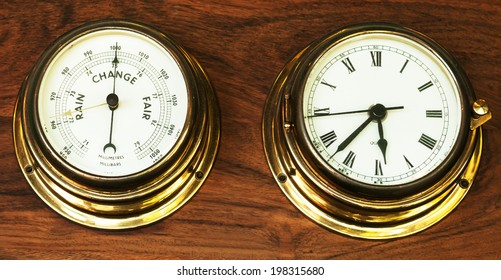 set of barometer and clock on wooden background