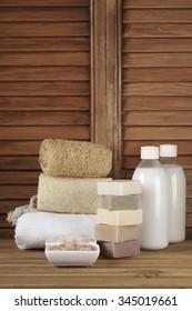 Set of bath accessory in wooden bathroom.