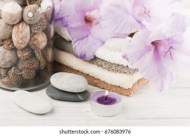 Set of bathroom accessory on wooden background: bottle, towels, pebbles, candles