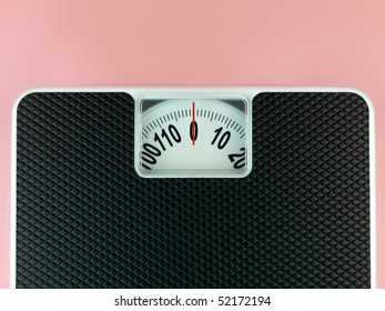 A set of bathroom scales isolated against a pink background