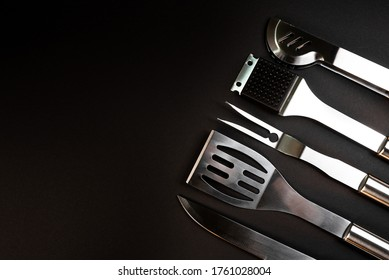 Set of BBQ equipment stainless steel as fork, spatula, tongs, knife, grill brush on black background
