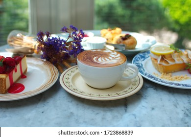 Set beautiful beverage and dessert consists hot latte coffee and strawberry cheesecake, lemon tart, scone, photogenic of food pastry lover on marble table blurred green tree in the garden background