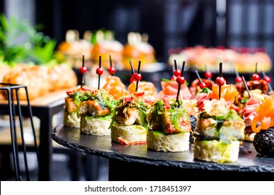 Set of beautiful canapes on black stone plates. Buffet table. Catering.
