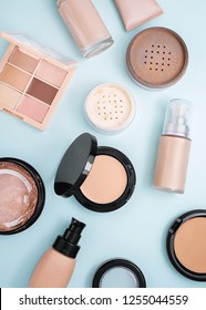Set of beauty products: brown face powder, beige shades concealer palette, foundations, golden highlighter, white loose powder on blue background.