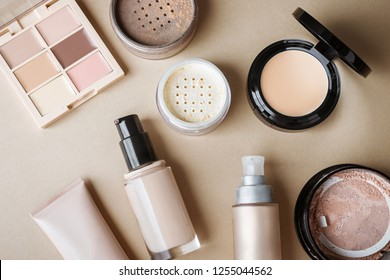 Set of beauty products: brown face powder, beige shades concealer palette, foundations, golden highlighter, white loose powder.