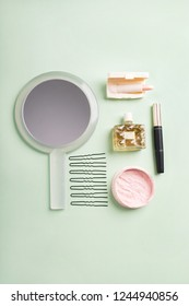 Set of beauty products: face powder, mascara, pale pink lipstick, perfume, hairpins, mirror on pale green background.