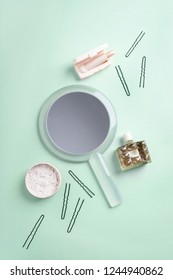 Set of beauty products: face powder, pale pink lipstick, perfume, hairpins, mirror on pale turquoise background.