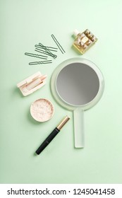 Set of beauty products: face powder, mascara, pale pink lipstick, perfume, hairpins, mirror on pale turquoise background.