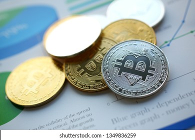 Set of bitcoin sign coins lying at stats graph paper closeup as idea of modern broker tool for success anti fraud buy and ambition education consultant career concept