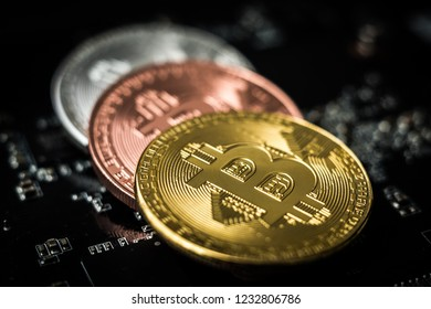 Set of bitcoins laying on computer motherboard, close-up. Stacked cryptocurrency coins with microcircuit