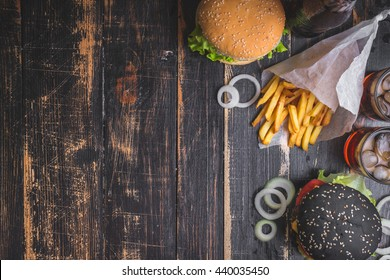 Set of black burgers with meat patty, cheese, tomatoes, mayonnaise, french fries and glass of cold cola soda with ice from above. Dark wooden rustic background. Space for text. Top view. Toned image
