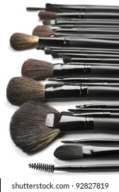 Set of black make-up brushes in row on white background.