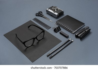 A set of black office accessories, glasses and old camera on gray background