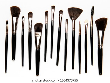 Set of black  professional makeup brushes with black handles  on white background. Top view, flat lay.