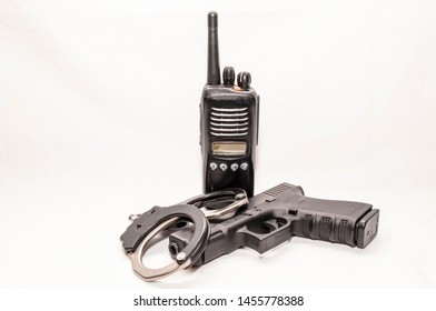 A set of black and silver handcuffs with a black 9mm pistol in front of a police radio with a white background