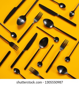 Set of black steel cutlery on bright yellow background. Top view point.