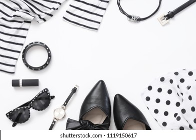 Set of black and white woman clothes and accessories on white background. Top view point, flat lay.