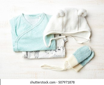 Set of blue baby clothes on wooden background, top view