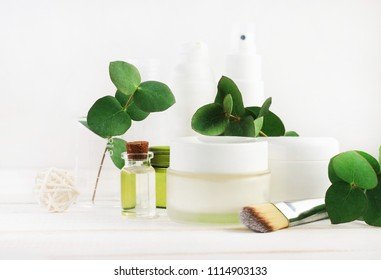 Set of bottles and jars with natural cosmetic products for skin care. White tones, green fresh leaves. Handcrafted essential oil, facial cream for holistic beauty treatment.