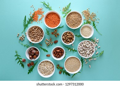 Set of bowls with organic quinoa, lentil, chickpea, wheat, walnut, almond, hazelnut and sesame. Cereals and legumes assortment on blue paper background. Top view. Copy space. Flat lay