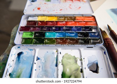 Set of bright saturated watercolor paints and brushes for painting. Mixed shades of paints on a plastic palette. Drawing and creative tools close-up. Selective soft focus.