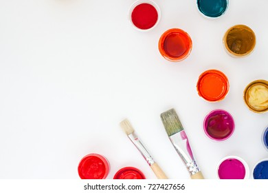 set of brightly colored paints with brushes on white table backround top view