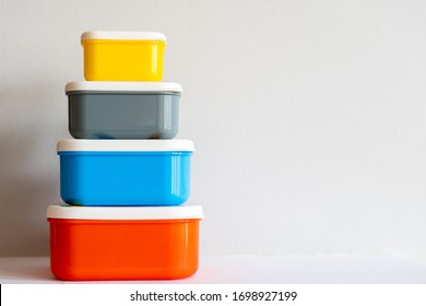 A set of brightly coloured (yellow, grey, blue, orange) plastic containers stacked by height against an off-white background