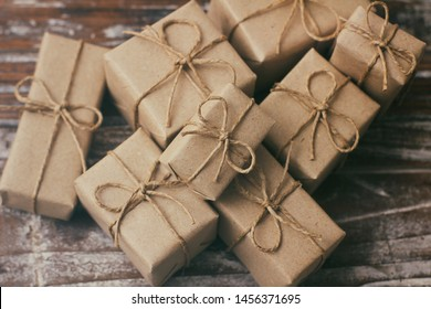 Set of brown gift boxes on wooden background. Wrapped in craft paper and tied by hemp cord. A lot of parcels.
