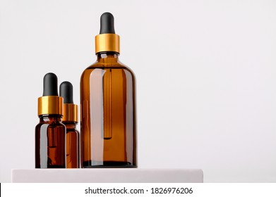 Set of brown glass bottles with essential oil on a white background on a stand. Packaging of a beauty product with a pipette for alternative medicine treatment. Aromatherapy, homeopathy. Copy space