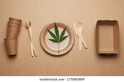 set of brown paper plates, cups and wooden forks and knives on a brown background, flat lay. View from above, plastic rejection concept, zero waste