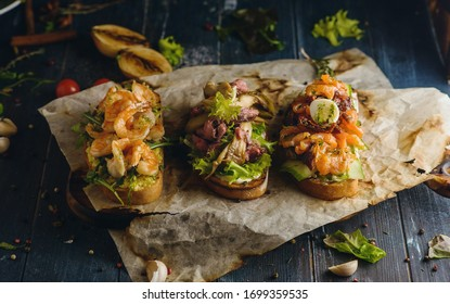 Set of bruschetta with roast beef, shrimps and salmon on dark wooden background among herbs, greens and ingredients