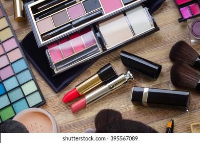 set of  brushes, lipsticks, maskara, eye shadows and  powder on wood