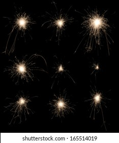 Set of burning sparklers isolated on black background. Small fireworks giving off sparks of fire. Sparks explosion.