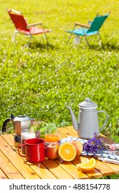Set of camping table full with food, fruit and coffee equipment outdoor with chairs.