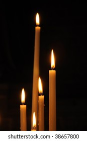 Set of candles in catholic church on dark background with only one in focus