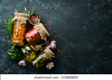 Set of canned vegetables and mushrooms in glass jars. Set of pickled food on black stone background. Top view.