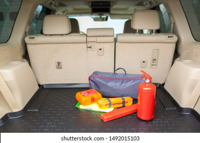 Set for a car from a fire extinguisher, tow rope, tool kit and medical kit in the trunk of an off-road vehicle.