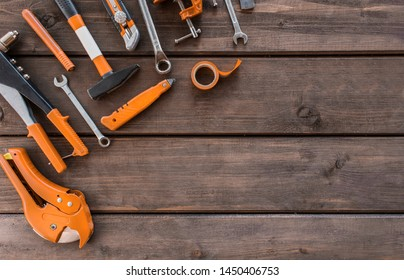 set of carpentry orange tools on wood background. carpenter working table. carpentry and woodwork industry flat lay concept top view