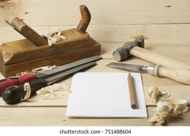 Set of carpentry tools in workshop. Paper and pencil in center of the table . Copy space for text.
