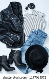Set of casual female clothes: black woolen hat, leather biker jacket, striped turtleneck , blue skinny jeans, leather ankle boots, pants belt on white background. Top view.