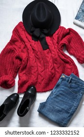 Set of casual female clothes: black woolen hat,knitted large viscous red sweater, blue skinny jeans, leather ankle boots, on white background. Top view.