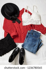 Set of casual female clothes: black woolen hat,knitted viscous red sweater, blue skinny jeans, leather ankle boots, fringed suede bag on white background. Top view.